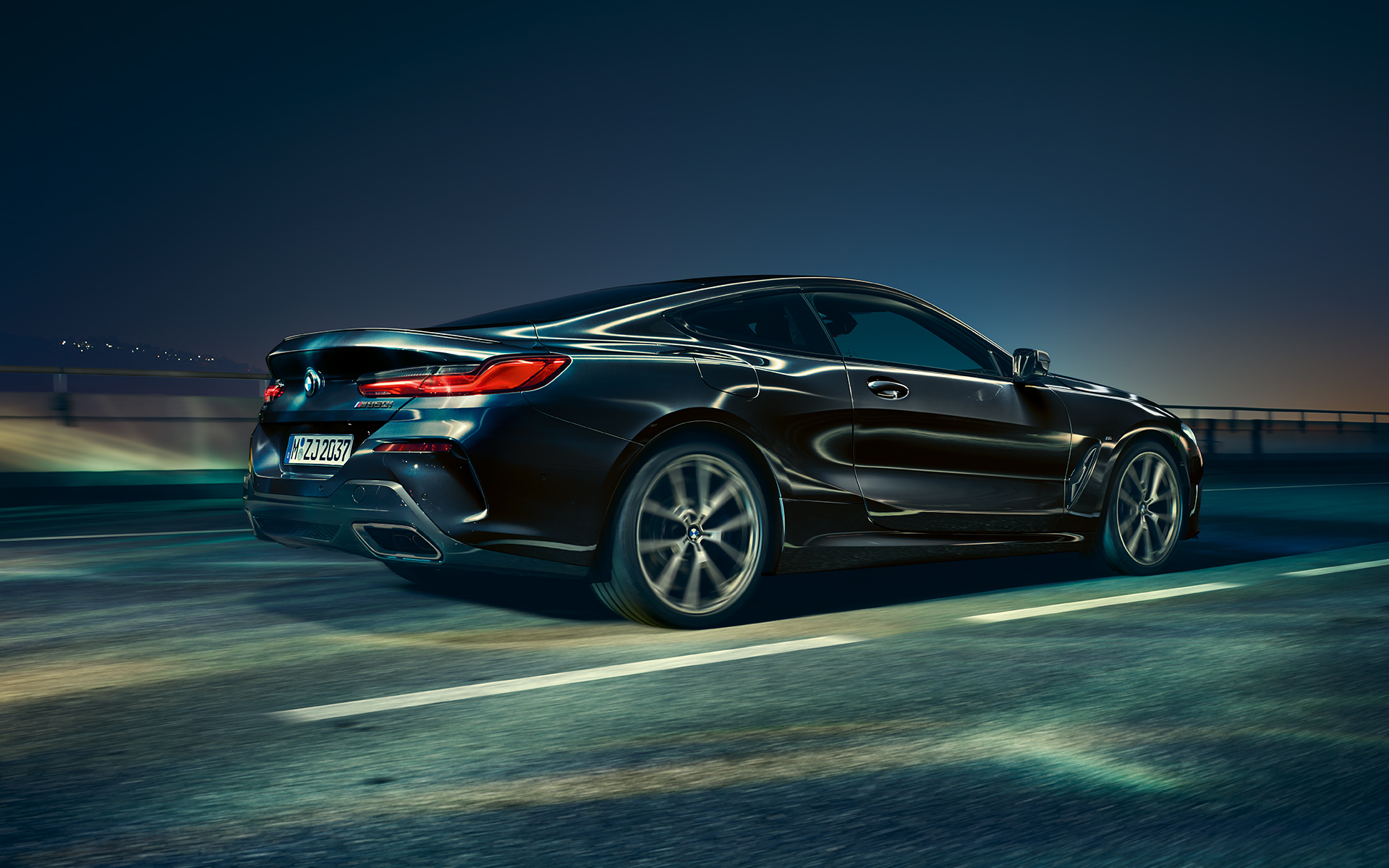 A three-quarter rear driving shot of the BMW 8 Series Coupé in an urban setting at night.