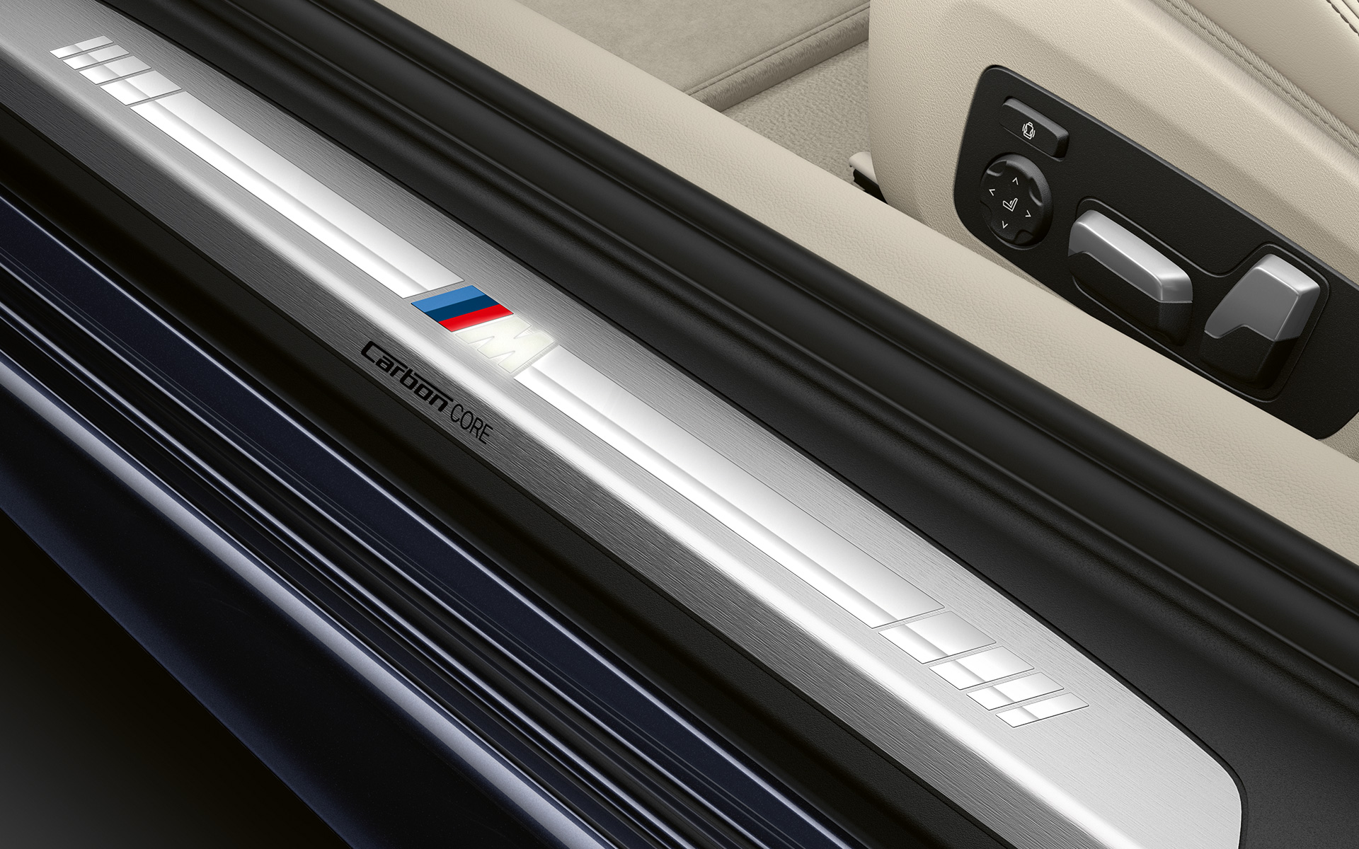 Close-up of the door sill of the BMW 8 Series Coupé with M logo.